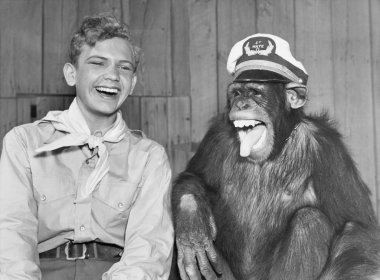Laughing boy scout and monkey wearing hat