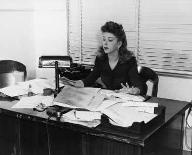 Woman working at desk covered in papers