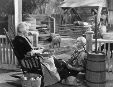 Elderly couple on porch of farmhouse