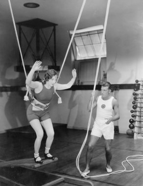 Female gymnast training with safety ropes with coach