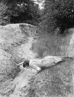 Woman drinking from tiny stream