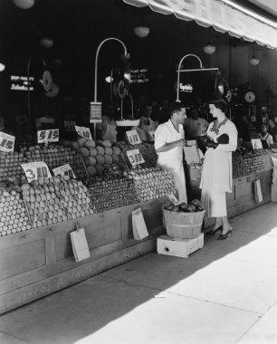 Woman and vendor at open air market
