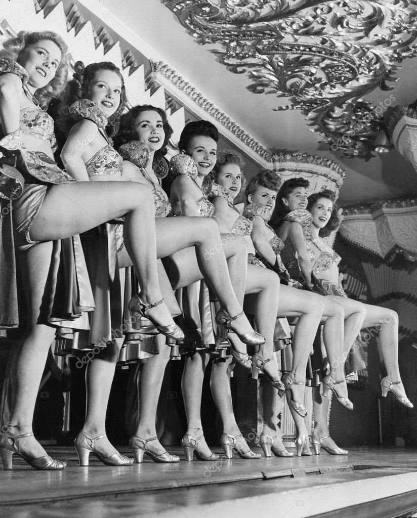 Chorus line of women with legs lifted