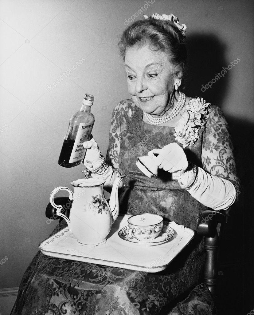 Elderly woman spiking her tea