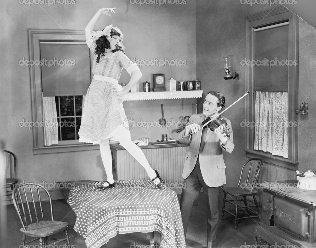Man playing violin for woman dancing on table