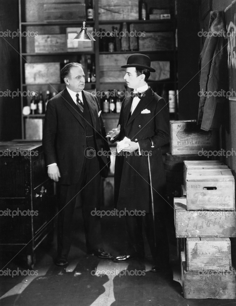 Businessmen conversing in storeroom