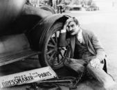 Muž se snaží opravit rozbité auto