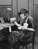 Portrait of woman at desk with letters