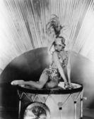 Fotografie portrét mladé ženy, sedící na buben s kloboukem pírko