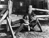 Fényképek Fiatal férfi ült egy kerítés mellett az ő kutia
