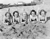 Portrét pěti mladých žen na pláži a s úsměvem