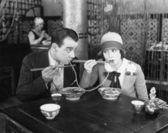 Fotografia coppia, condivisione di una tagliatella in un ristorante