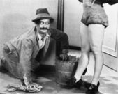 Photo Man cleaning the floor looking at the legs of a woman