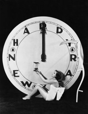 Woman with clock at midnight on New Years Eve