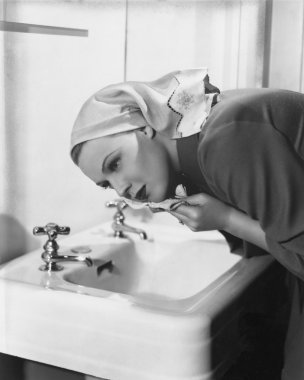 Woman washing face over sink