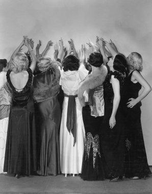 Rear view of women reaching