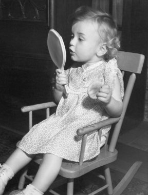 Little girl looking in mirror