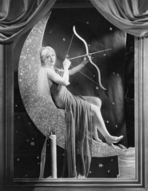 Woman sitting on crescent moon with bow and arrow