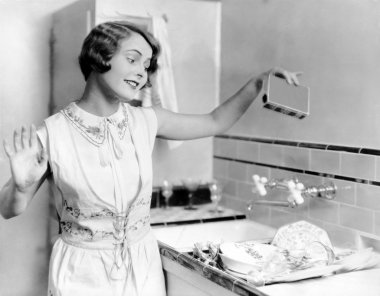 Woman pouring soap on dishes
