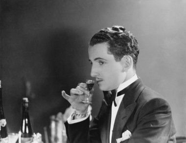 Man drinking glass of liqueur