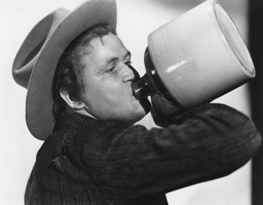 Portrait of man drinking from jug