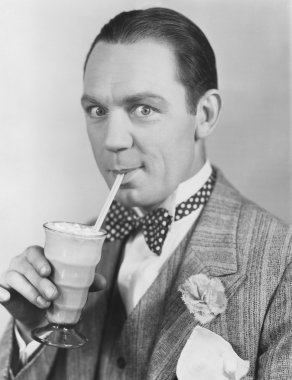 Portrait of man drinking through straw