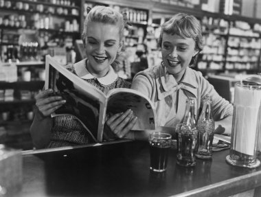 Girlfriends looking at magazine at soda fountain