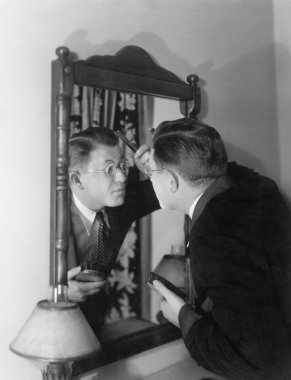 Man at mirror combing hair