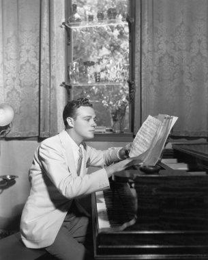 Man at piano with sheet music