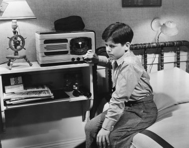 Boy listening to radio in bedroom