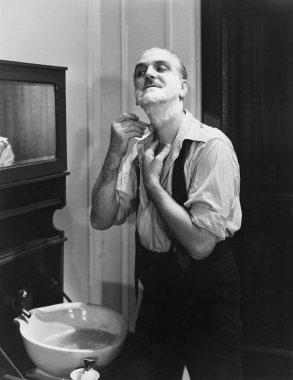 Portrait of man shaving
