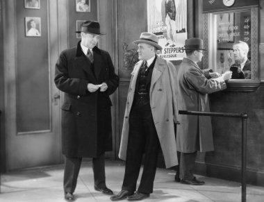 Men talking in theater lobby
