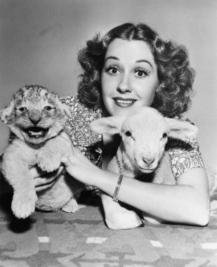 Woman with lamb and lion cub
