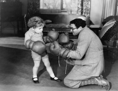 Father and young son playing with boxing gloves