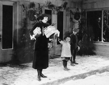 Woman and children outside with Christmas presents