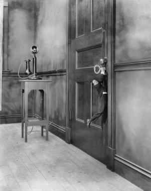 Tiny man hanging from key in door