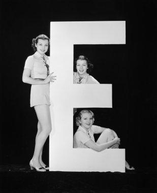 Women posing with huge letter E