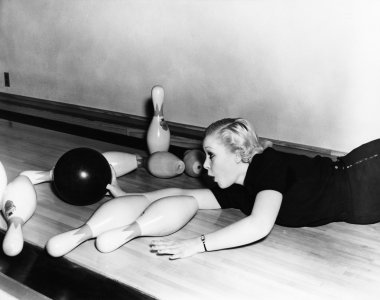 Woman sliding down bowling alley with ball