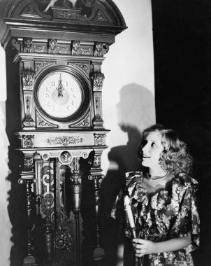 Woman with grandfather clock at midnight