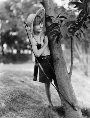 Boy behind tree with bow and arrow