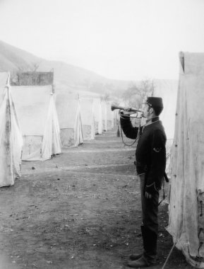Soldier blowing bugle in army camp