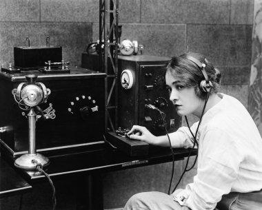 Woman sending Morse code using telegraph