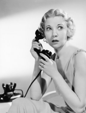 Shocked woman on telephone