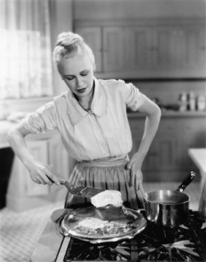 Woman flipping eggs on stove