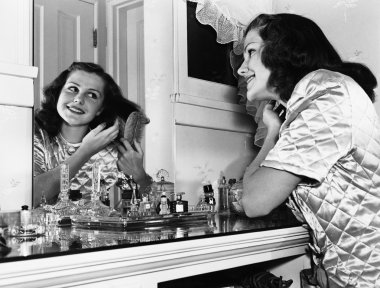 Young woman brushing hair at dressing table