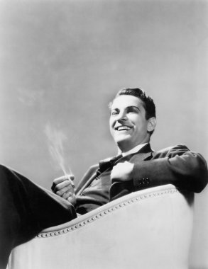 Man sitting in an arm chair smoking