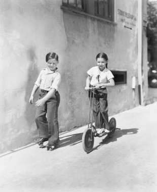 Boy and girl playing on a scooter and the other on roller blades