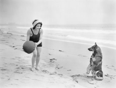 Young woman playing with her dog and ball on the beach