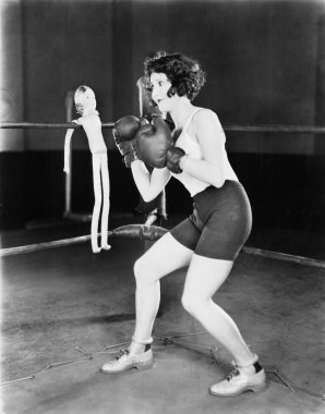 Young woman with boxing gloves with a doll on the ropes