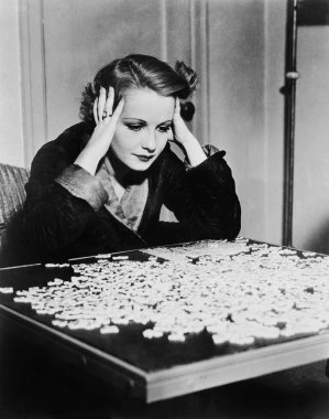 Young woman trying to solve a puzzle